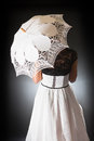 Retro bride with lace umbrella a white a white silk dress and a black top seen from the back she is lighted backlight Royalty Free Stock Photo