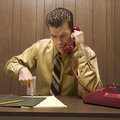 Retro business scene of angry man at desk. Royalty Free Stock Photography