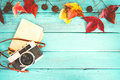 Retro camera and empty old instant paper photo album on wood table with maple leaves in autumn border design
