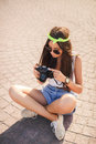 Retro camera shoots girl in the streets of the city. Royalty Free Stock Photo