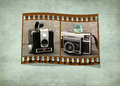 Retro cameras in filmstrip pair of film strip frame on green textured background Royalty Free Stock Photos