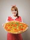 Retro casalinga che tiene una pizza vegetariana Immagine Stock Libera da Diritti