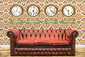 Retro chesterfield sofa with world time clocks on a wall Royalty Free Stock Photo