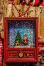 Retro Christmas Ornament - Vintage red television set with santa & snow scene behind plastic - Rustic background blurred Royalty Free Stock Photo