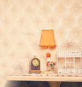 Retro clock, lamp and birdcage backdrop. Royalty Free Stock Photo