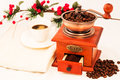 Retro coffee mill and cup of coffee on white background