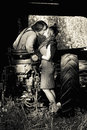 Retro couple kissing in s clothing on tractor Stock Photography