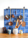 Retro design kitchen interior with accessories. Hanging copper kitchenware set. Pot, stewpot, spoon, skimmer, ladle Royalty Free Stock Photo