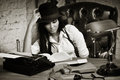Retro detective girl sits at a table in the agency Royalty Free Stock Photos