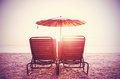Retro filtered picture of beach chairs and umbrella on sand.
