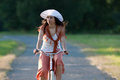 Retro girl on old bike woman in orange skirt and white hat riding a in meadow view from the front Stock Photos