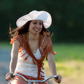 Retro girl on old bike woman in orange skirt and white hat riding a in meadow view from the front Royalty Free Stock Photos