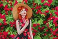 RRetro girl with red lips in a dress with a print of roses with ice cream on summer background. Young redhead model in a hat Royalty Free Stock Photo