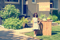 Retro girl wearing sunglasses with lemonade stand in the front yard Royalty Free Stock Photo