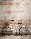 Retro hipster bicycle in front of the old brick wall, background