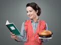 Retro housewife with cookbook smiling holding a and a baking tin a homemade cake Stock Photo