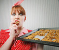 Retro housewife stressed sneaking cookies Royalty Free Stock Photo