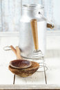 Retro kitchen utensils tools on old wooden table in rustic style and wood wall Stock Photography
