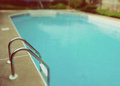 Retro look swimming pool ladder selective focus view of with film treatment Royalty Free Stock Photos