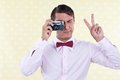 Retro male using old camera man looking through making peace sign Stock Photo