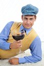 Retro man with large wine glass leaning on rug Royalty Free Stock Image