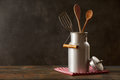 Retro milk can with kitchenware on wooden table Royalty Free Stock Photo