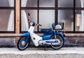 Retro motorcycle blue japanese in front of japanese style window Royalty Free Stock Photo