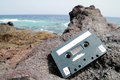 Retro musicassette ancient on the rocks near the beach Royalty Free Stock Photo