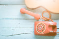 Retro orange-red telephone and the guitar Royalty Free Stock Photo