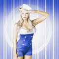 Retro photograph of a navy blue american sailor girl posing for a military salute on pinup blue stripes Royalty Free Stock Images