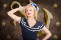 Retro pin up sailor woman retro s fashion style portrait of a beautiful young blond wearing navy hat saluting in in front of old Royalty Free Stock Photo