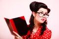 Retro. Pinup girl in eyeglasses reading book Royalty Free Stock Photo