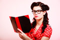 Retro. Pinup girl in eyeglasses reading book Royalty Free Stock Photo