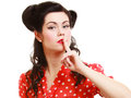 Retro pinup girl with finger on lips asking for silence style woman hush hand gesture isolated white brunette or secrecy Royalty Free Stock Image