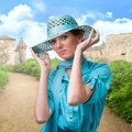 Retro portrait of a woman in a turquoise hat collage with old castle as a background Stock Photos
