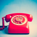 Retro red telephone over blue background Royalty Free Stock Images