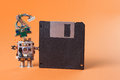 Retro robot with floppy disk. Creative design character blue eyed head, electrical wire hairstyle. Copy space, orange Royalty Free Stock Photo