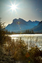 Retro rundle mountain sun rising over and vermilion lake with lens flare and aged vintage processing banff national park canada Stock Photos