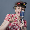 Retro singer in studio with s female performing artist fifties style singing old fashioned microphone closeup over gray Stock Images