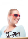 Retro spectacles or glasses with heavy black frames on a wooden table top with a blurred woman wearing sunglasses laughing in the Royalty Free Stock Photos