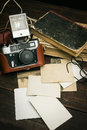 Retro Still Camera And Some Old Photos On Wooden Table Background
