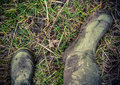 Retro style photo of rubber boots faded dirty in the countryside Royalty Free Stock Photos