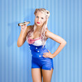 Retro style pin up sailor girl on blue background pinup holding contracted monocular maritime stripe Stock Photo