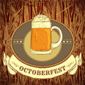 Retro styled emblem with cup of beer, ribbon banner and the text Beer festival Oktoberfest on wooden background.