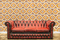 Retro styled image old sofa against vintage wallpaper wall brown orange flower print Stock Photo