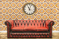 Retro styled image of an old sofa and clock against a vintage wa wallpaper wall with flower print Stock Photos