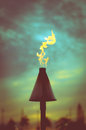 Retro styled tiki torch filtered vacation image of a hawaiian at sunset Royalty Free Stock Photo
