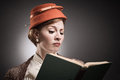 Retro styled woman reading a book in garb Stock Images