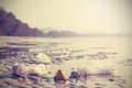 Retro stylized picture of garbage on a beach. Royalty Free Stock Photo