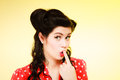 Retro surprised pinup girl with finger to mouth style woman her hand gesture on yellow portrait of shocked brunette Stock Photography